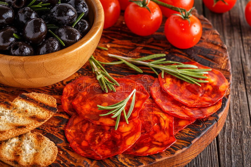 Saucisse traditionnelle espagnole de chorizo avec les herbes fraîches, olives photographie stock