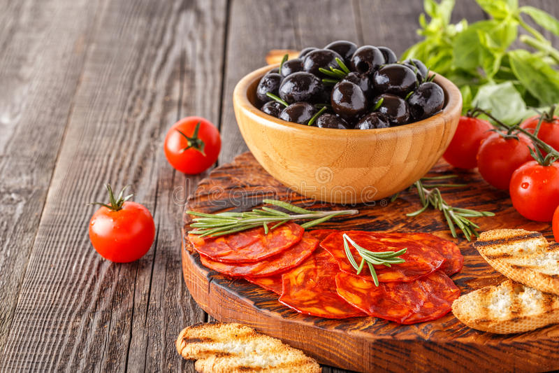 Saucisse traditionnelle espagnole de chorizo avec les herbes fraîches, olives photo libre de droits