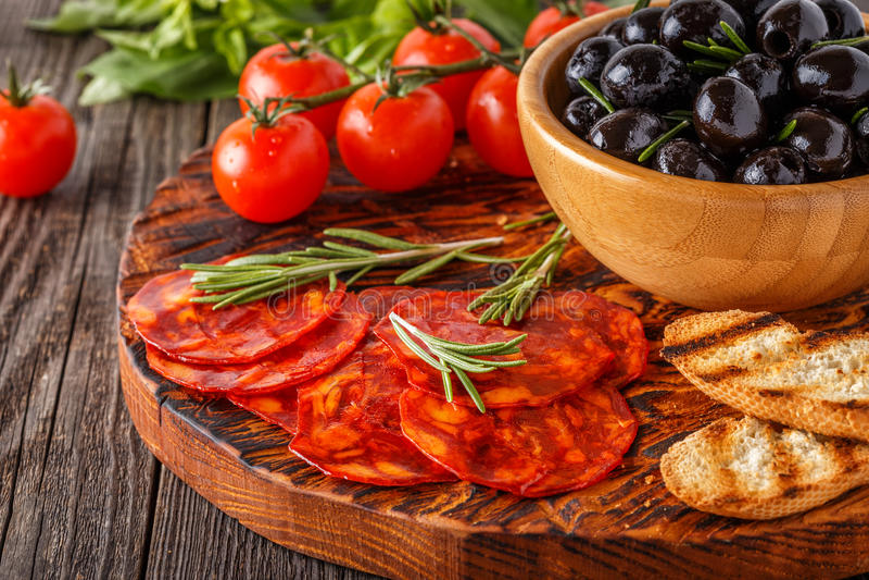 Saucisse traditionnelle espagnole de chorizo avec les herbes fraîches, olives photo stock