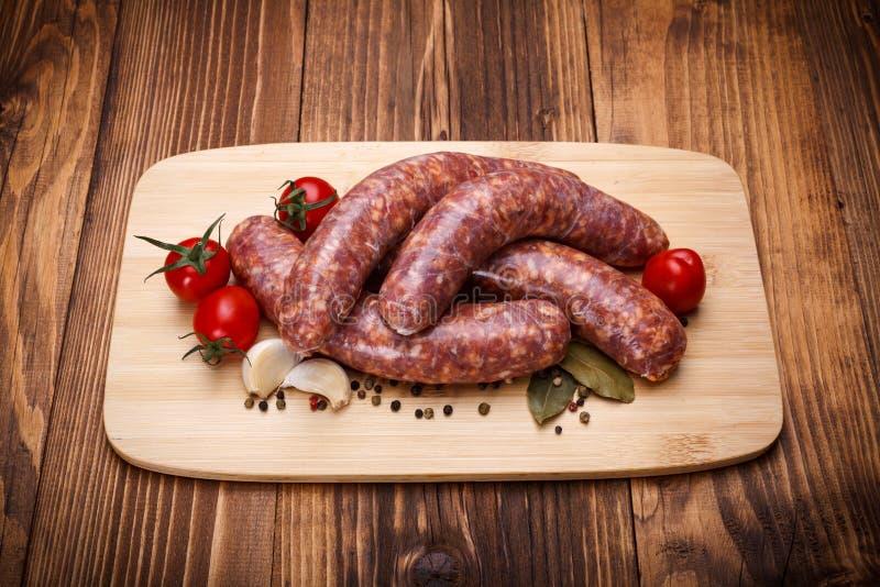 Saucisses épaisses de porc cru sur la planche à découper photo stock