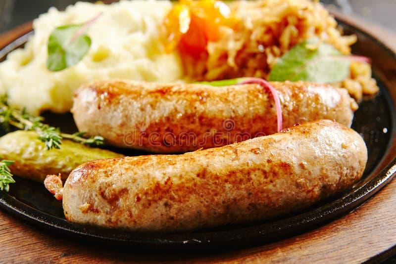 Saucisses allemandes traditionnelles avec de la purée de pommes de terre et la choucroute image stock