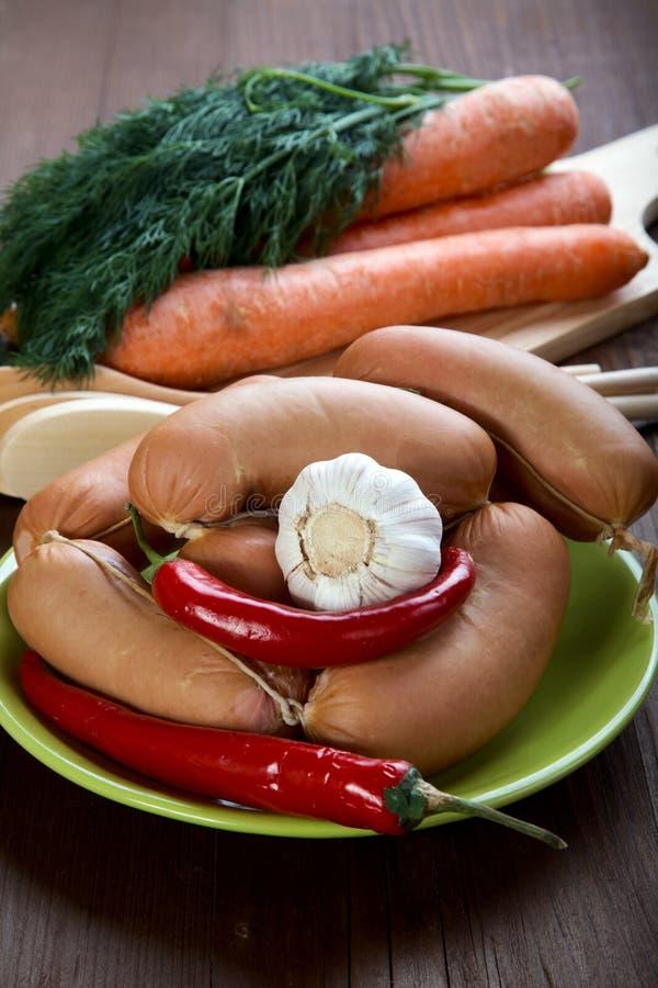 Saucisses avec des épices et des légumes images stock
