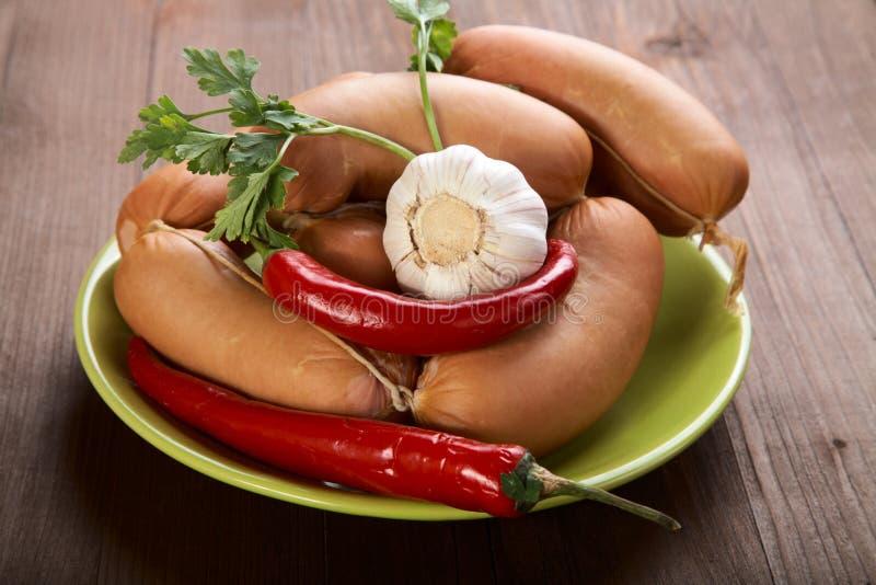 Saucisses avec des épices et des légumes photos libres de droits