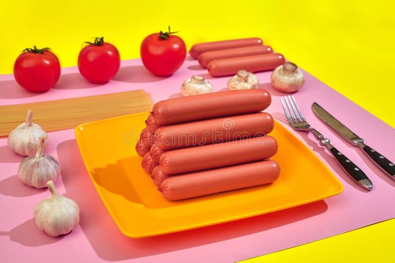 Saucisses avec des tomates, des spaghetti et l'ail sur un fond minimal jaune et rose Configuration plate Vue supérieure images stock