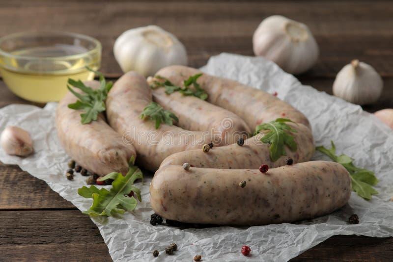 Saucisses crues avec des ingrédients pour faire cuire l'arugula, le beurre et l'ail Sur une table en bois brune photographie stock libre de droits