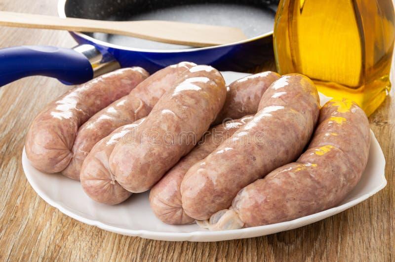 Saucisses crues dans la coquille naturelle sur le plat blanc, poêle, spatule, huile végétale sur la table en bois image stock