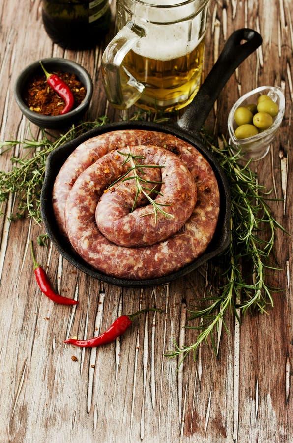 Saucisses crues de boeuf sur une casserole de fonte, foyer sélectif photos stock