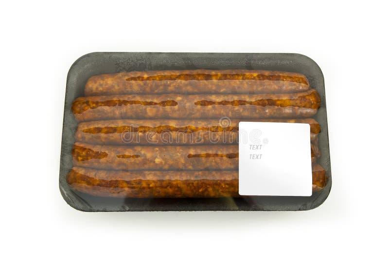 Saucisses dans un paquet avec un autocollant photographie stock libre de droits
