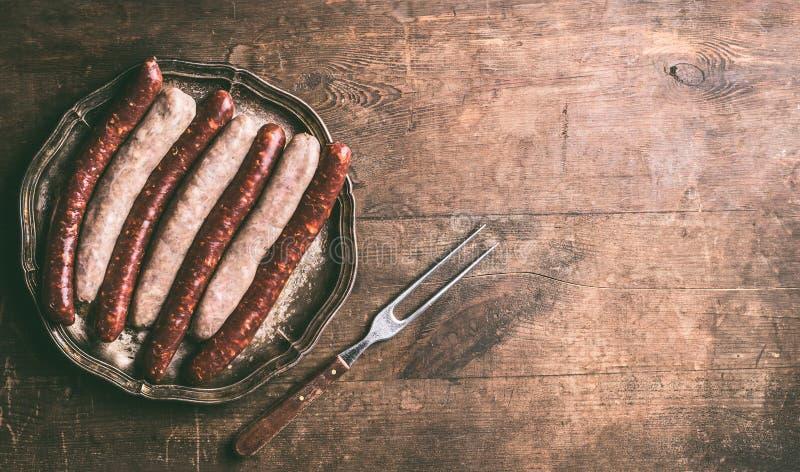 Saucisses de boeuf et de proc pour le gril ou le BBQ du plat foncé de vintage avec la fourchette de rassemblement sur le fond en  photos libres de droits