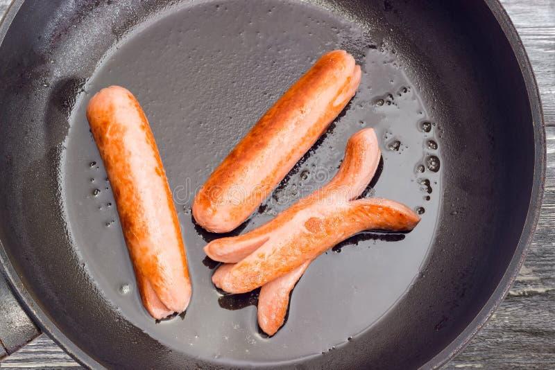 Saucisses de Francfort frites sur le plan rapproché de poêle photos libres de droits