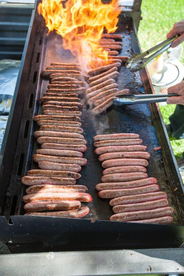 Saucisses de gril de flamme sur un barbecue photo libre de droits