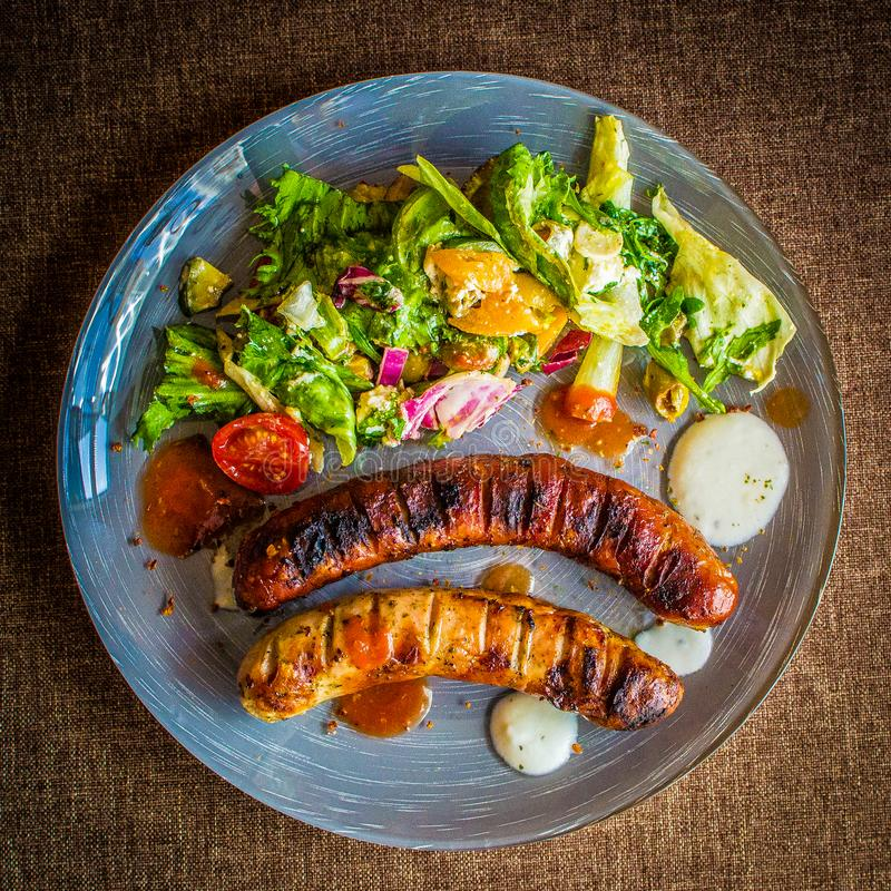 Saucisses de grils avec de la salade photos stock