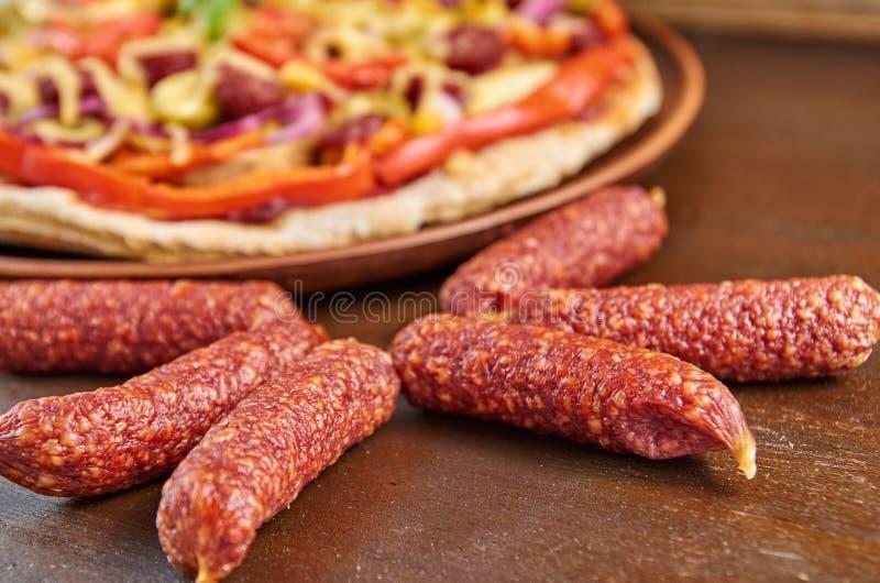 Saucisses de salami d'isolement sur la fin en bois brune de table  Sur le fond brouillé a coupé en tranches la pizza avec le sala photographie stock libre de droits