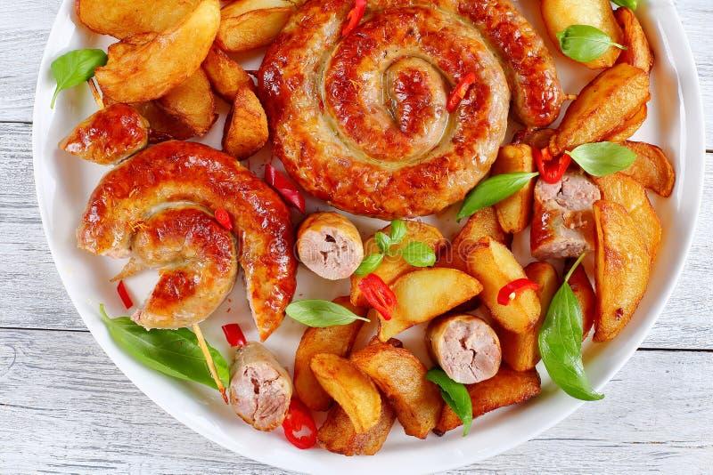 Saucisses en spirale frites rondes sur le plat blanc images stock