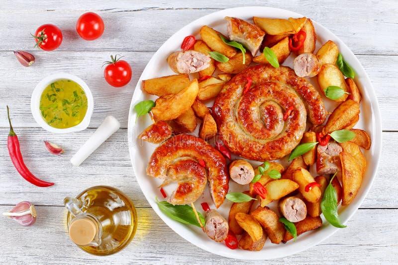 Saucisses et pomme de terre frites chaudes sur le plateau photographie stock