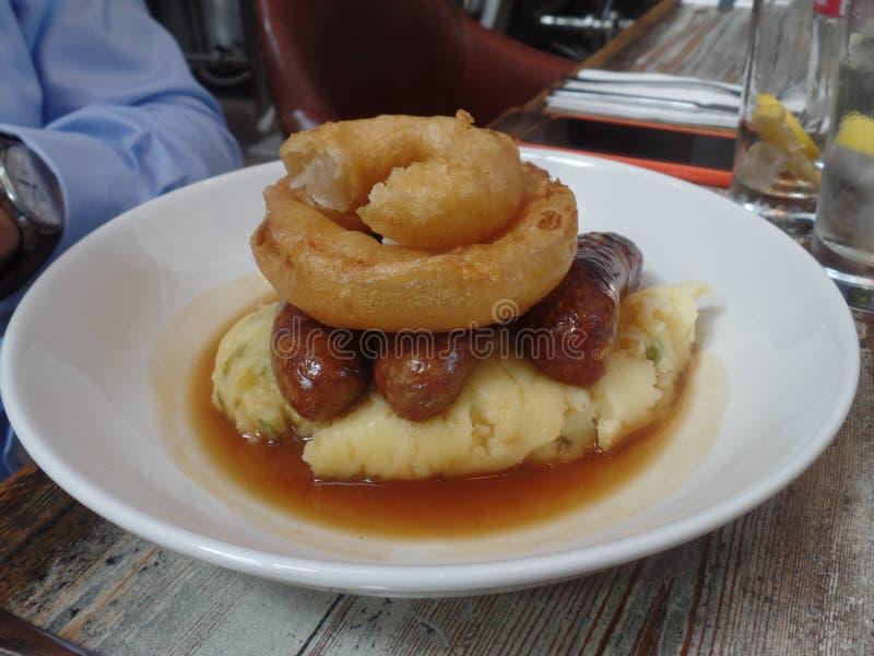 Saucisses et purée de pommes de terre d'un plat blanc image libre de droits
