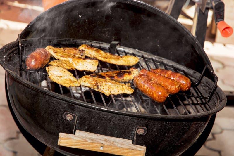 Saucisses et viande de poulet sur un gril images stock