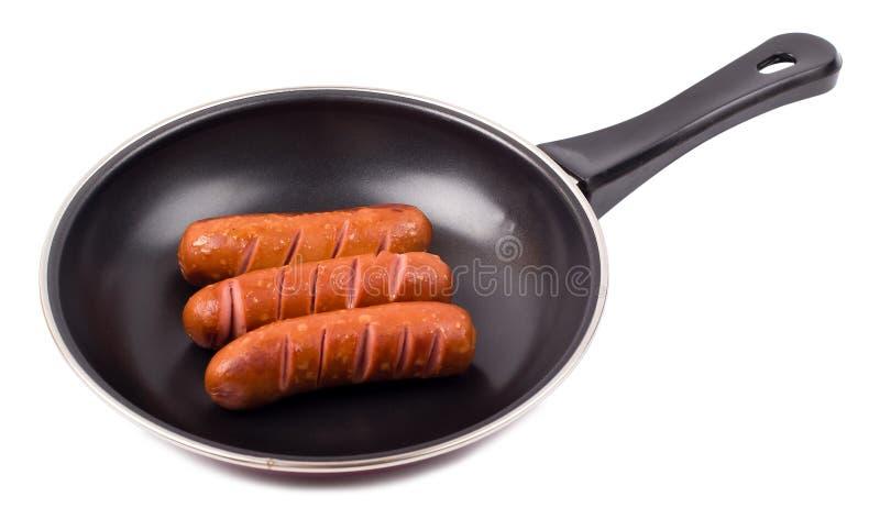 Saucisses frites dans une poêle images stock