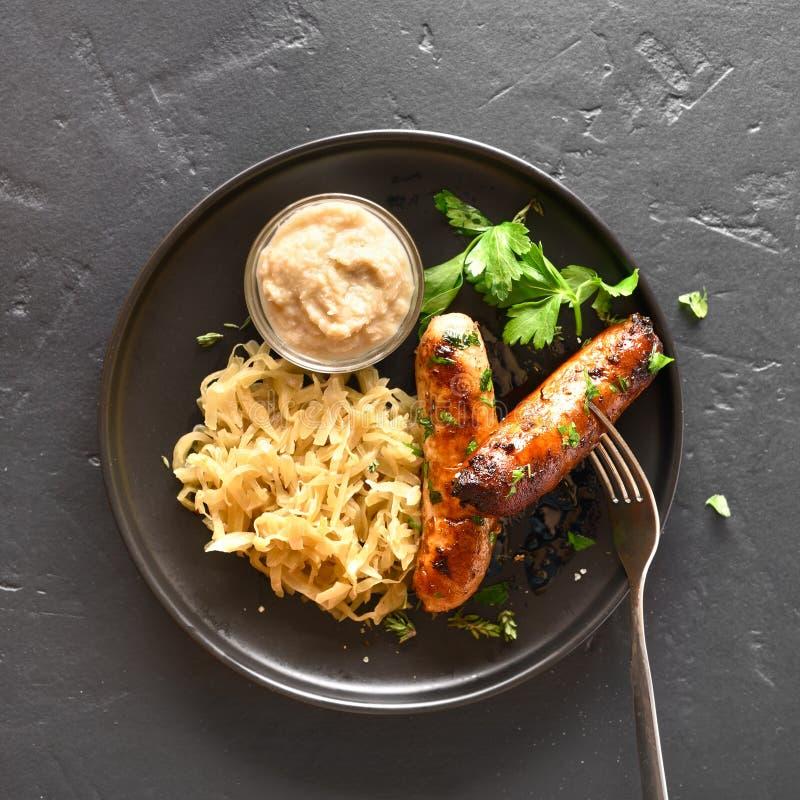 Saucisses grill?es avec la choucroute et le raifort photos stock
