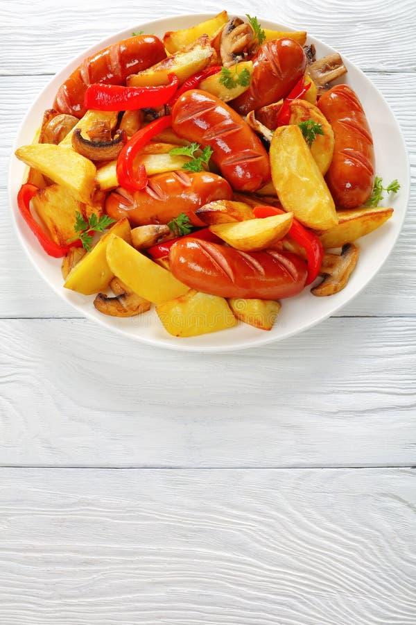 Saucisses grillées avec les cales frites de pommes de terre photographie stock