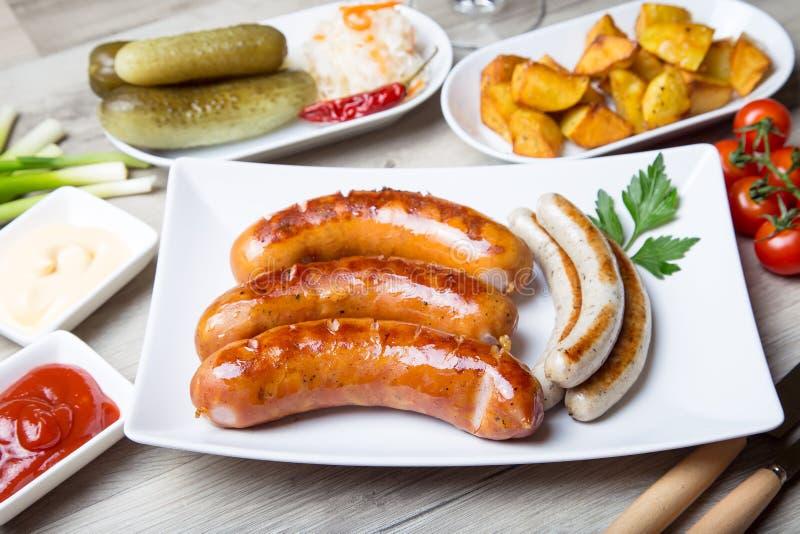 Saucisses grillées avec les pommes de terre, concombres et choucroute, avec des deux sauces photo libre de droits