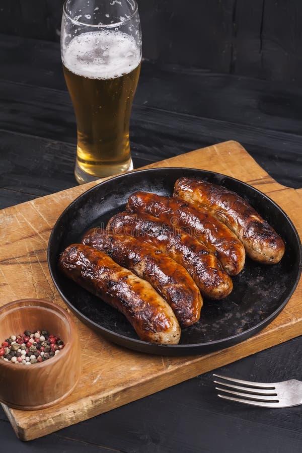 Saucisses grillées juteuses de poulet sur un fond en bois foncé images libres de droits