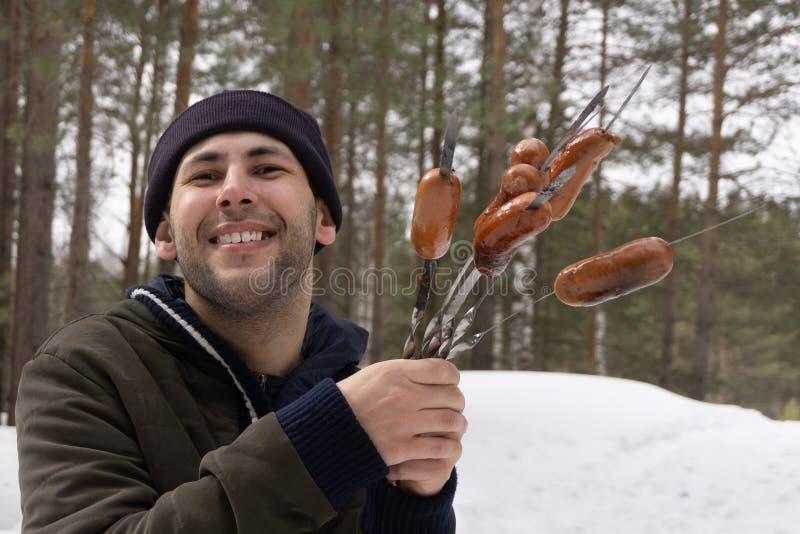 Saucisses grillées par homme au-dessus de firecamp photos libres de droits