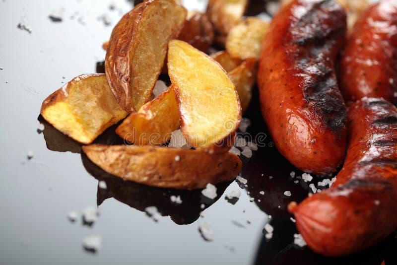 Saucisses grillées Pommes de terre cuites au four closeup Sur la surface de miroor Paraboloïde savoureux images stock