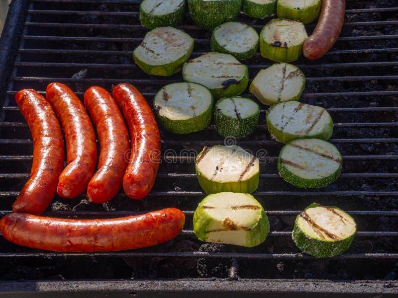 Saucisses grill?es les saucisses de fromage font frire sur le gril avec la courgette photographie stock libre de droits