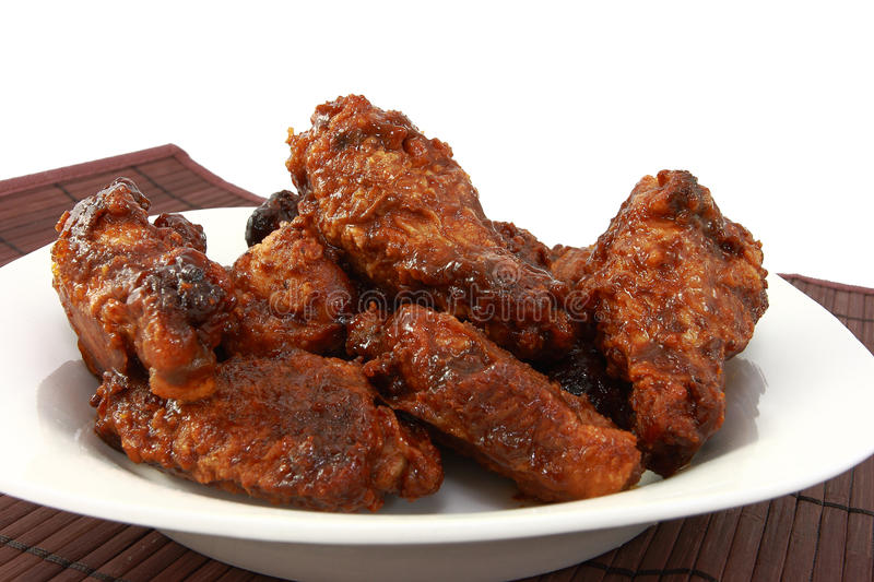 Saucy Chicken Wings In A White Dish. Chicken wings coated with a red sauce and piled on a white plate stock photos