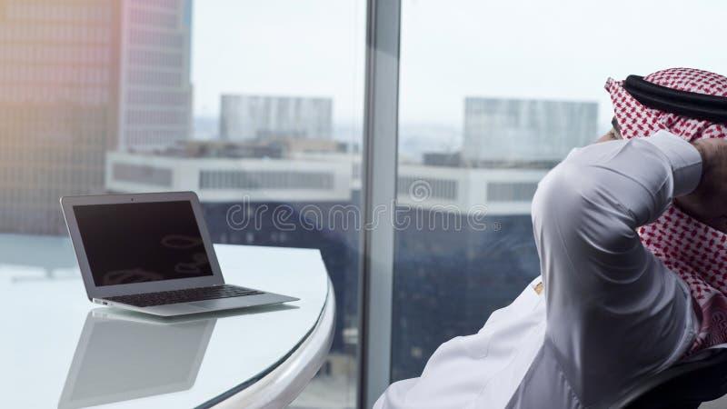 Saudi Arab Man Watching Laptop at Work Contemplating. Saudi Arab Man Watching Laptop at Work and Contemplating royalty free stock images