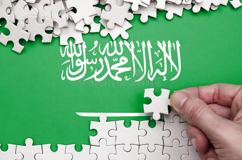 Saudi Arabia flag is depicted on a table on which the human hand folds a puzzle of white color stock photos