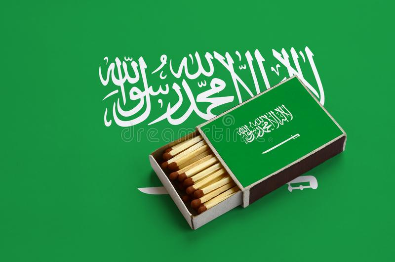 Saudi Arabia flag is shown in an open matchbox, which is filled with matches and lies on a large flag stock photo