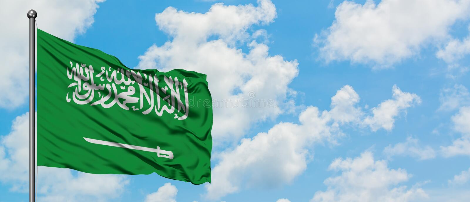 Saudi Arabia flag waving in the wind against white cloudy blue sky. Diplomacy concept, international relations.  stock photography