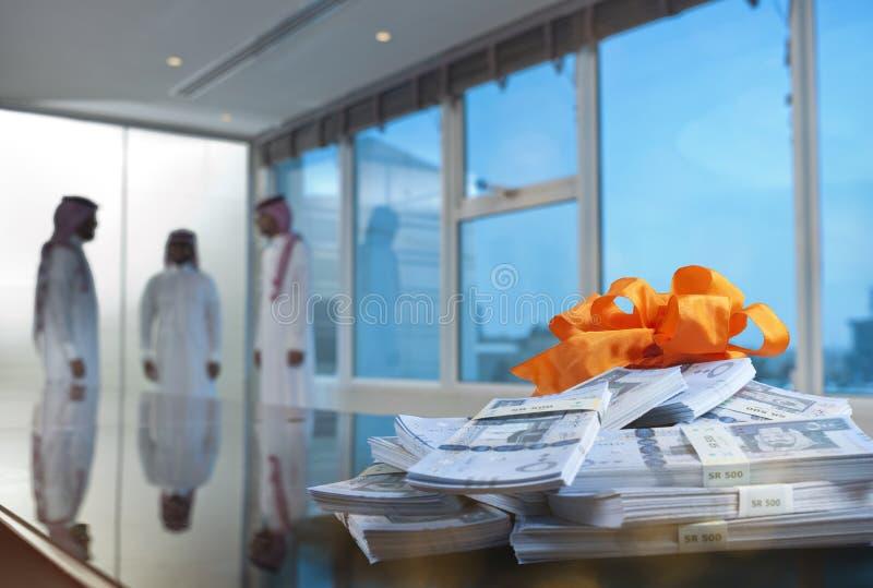 Saudi-arabische Geschäftsmänner in einem Konferenzzimmer mit Stapeln Geld an stockbilder