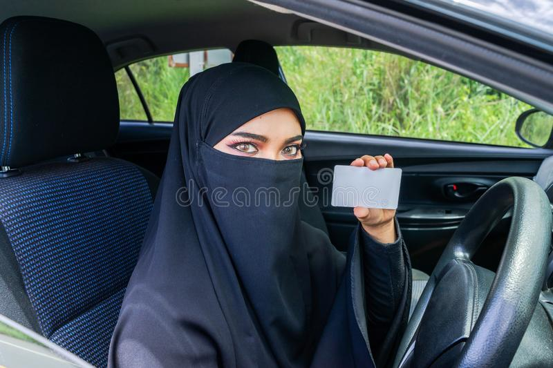 Saudi Woman Driving a Car on the road. Saudi Woman Driving a Car on the road and showing a blank driving licence for graphic montage. Muslim Woman Driver royalty free stock photography