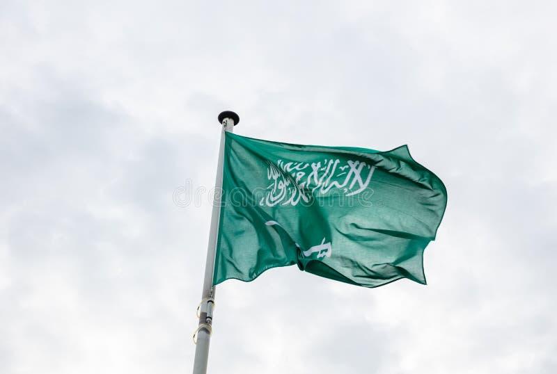 Saudiarabien flagga på en pol som vinkar, bakgrund för molnig himmel arkivbilder