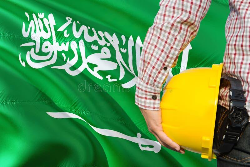 Saudyjski inżynier trzyma żółtego zbawczego hełm z machać Arabia Saudyjska chorągwianego tło Budowy i budynku poj?cie fotografia royalty free