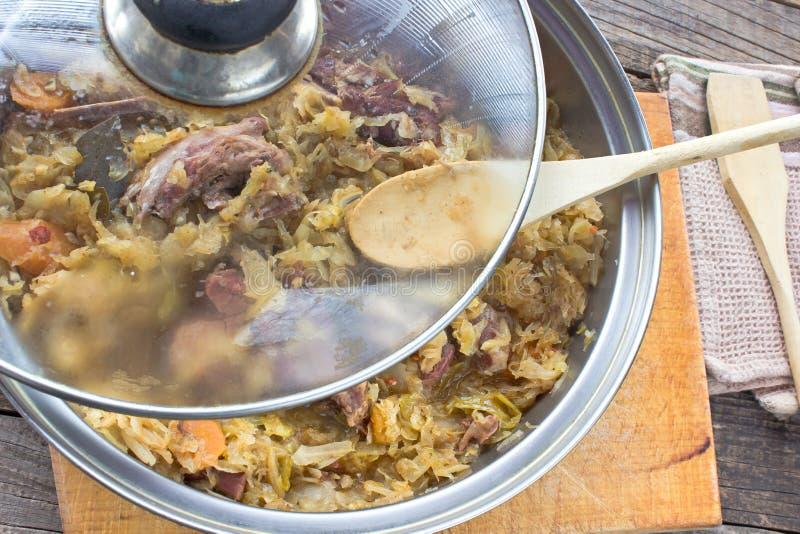 Sauerkraut с копченым мясом свинины в баке стоковая фотография
