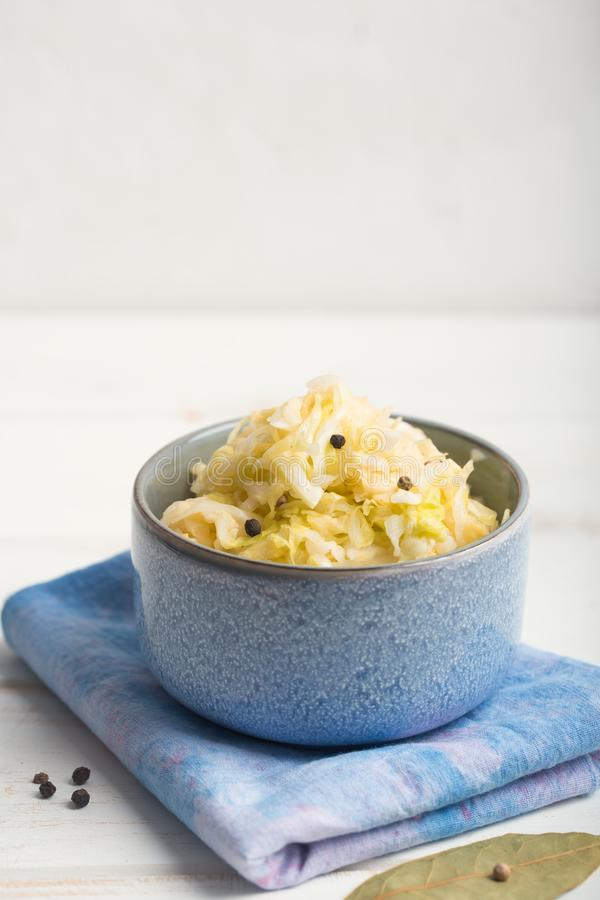 Sauerkraut in a blue bowl on a wooden table. Sauerkraut is fermented cabbage. Typical fermented food in some countries such as Russia. Poland or German. It is stock photos