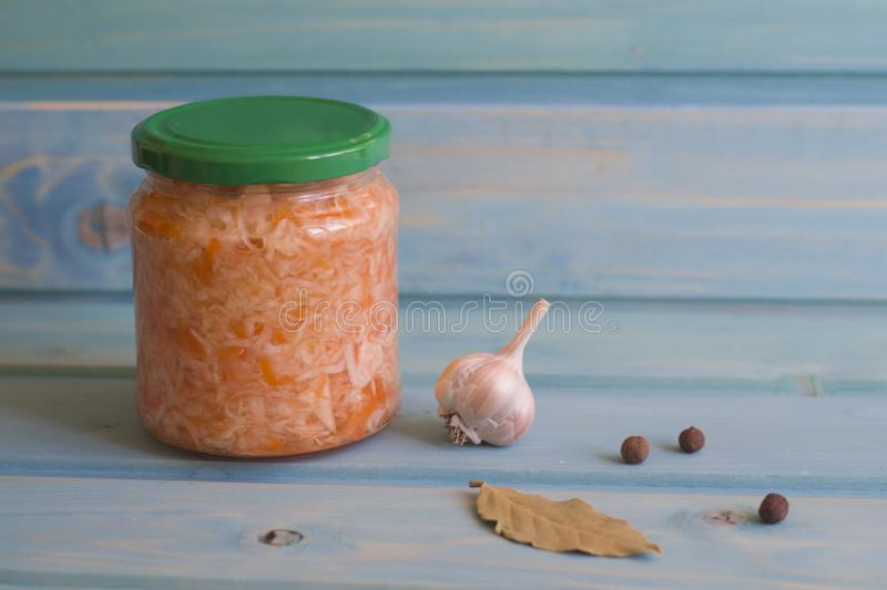 Sauerkraut with carrots in jars on a blue wooden background royalty free stock photography