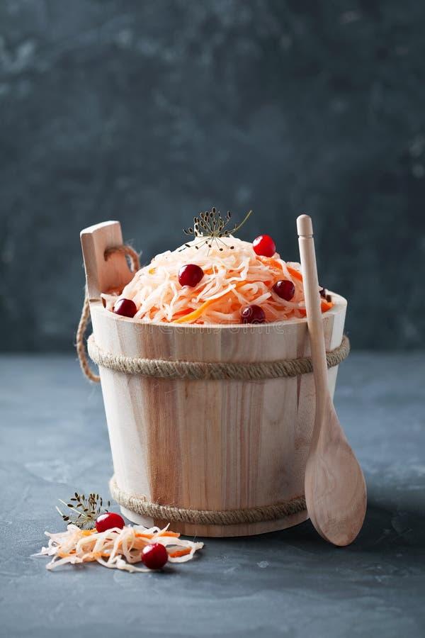 Sauerkraut mit Karotten und Moosbeeren im hölzernen Eimer stockbild