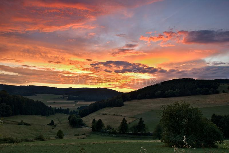 Sauerland, Γερμανία - δραματικό ρόδινο και πορτοκαλί ηλιοβασίλεμα πέρα από μια πράσινη κοιλάδα με τους δασώδεις λόφους στην απόστ στοκ φωτογραφία