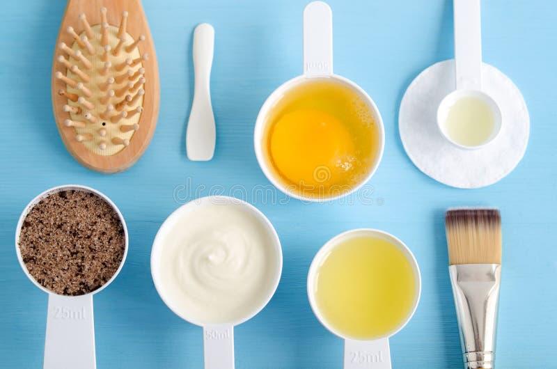 Sauerrahm oder griechischer Jogurt, roher Ei-, gemahlenerkaffee mit braunem Zucker und Olivenöl in kleine Schaufeln Bestandteile  stockfotografie