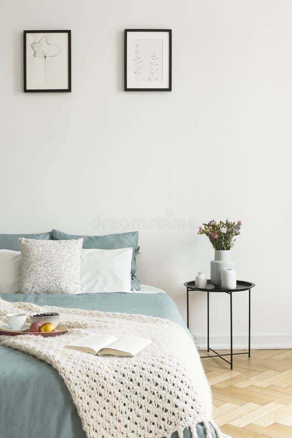 Sauge pâle et toile blanche, oreillers et une couverture sur un lit se tenant contre le mur blanc avec deux photos dans un intéri photo stock