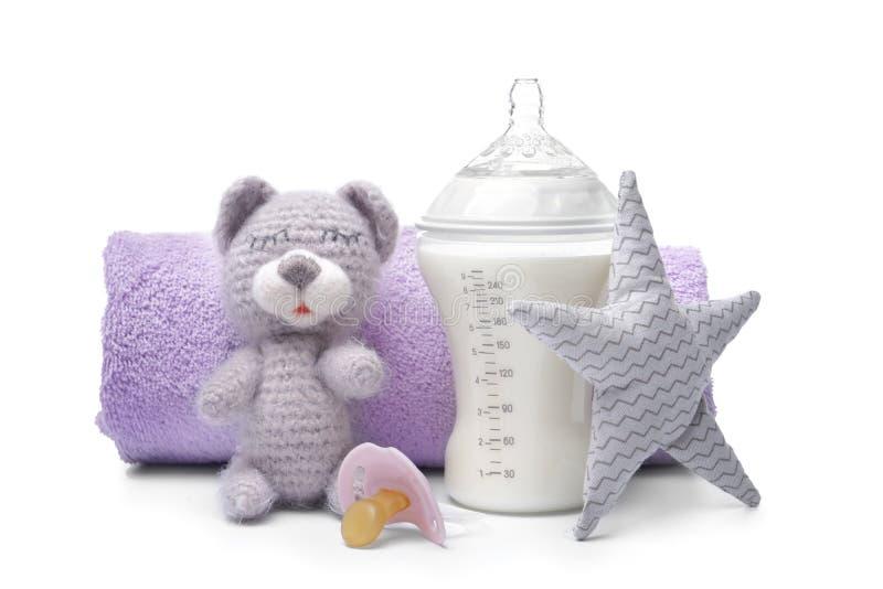 Saugflasche der Milchnahrung mit Spielwaren und Tuch auf weißem Hintergrund stockfoto