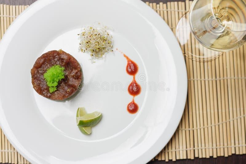 Saumons avec de la sauce et la chaux à tartre du plat blanc simple photos stock