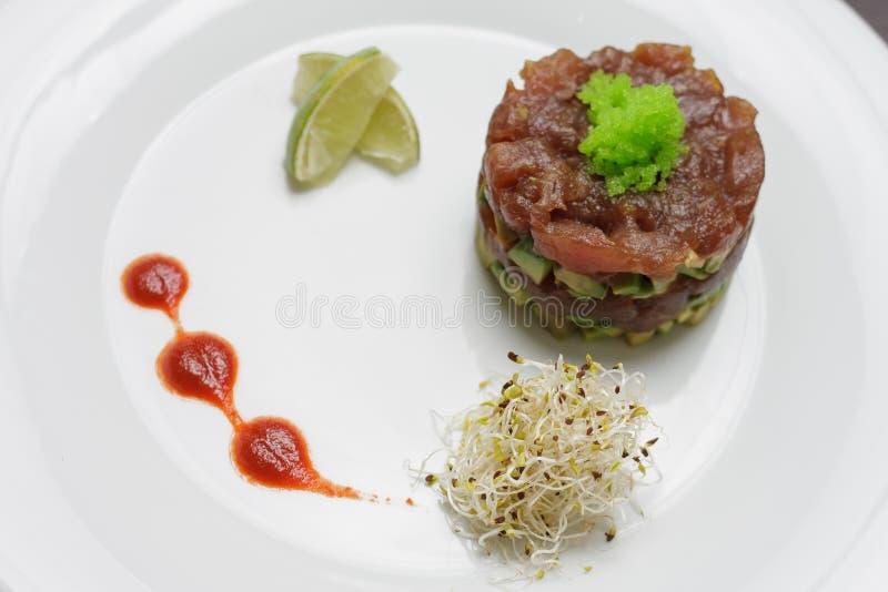 Saumons avec de la sauce et la chaux à tartre du plat blanc simple image libre de droits