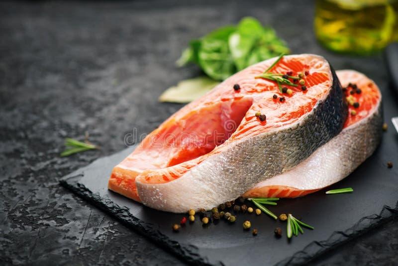 Saumons Bifteck de poissons cru de truite avec des herbes sur le fond noir d'ardoise Cuisson, fruits de mer Consommation saine photo libre de droits