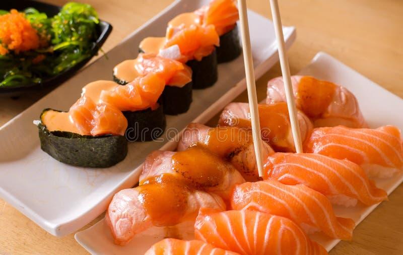Saumons de baguettes et de sushi sur le plat dans le restaurant, style japonais images stock